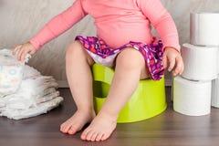 A menina senta-se em um potenciômetro verde e aprende-se a higiene elementar, comutando dos tecidos a um toalete fotos de stock royalty free