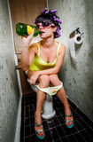A menina senta-se em um toalete Fotos de Stock Royalty Free