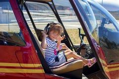 A menina senta-se em um volante do helicóptero Imagem de Stock Royalty Free