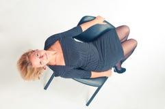 A menina senta-se em uma cadeira Fotos de Stock Royalty Free