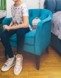 A menina senta-se em uma cadeira azul do vintage Fotos de Stock Royalty Free
