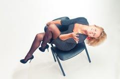 A menina senta-se em uma cadeira e é-se pesarosa Imagem de Stock