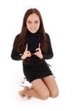 A menina senta-se em uma cadeira e em guardar um tablet pc Fotos de Stock Royalty Free