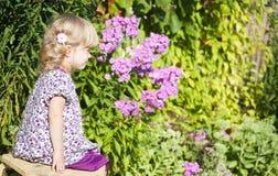 A menina senta-se em uma cadeira em um jardim fotos de stock