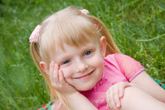A menina senta-se em uma grama Fotos de Stock Royalty Free