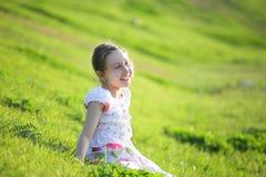 A menina senta-se em uma grama Foto de Stock