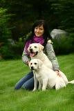 A menina senta-se em uma grama com dois cães Fotos de Stock