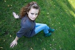 A menina senta-se em uma grama verde Fotos de Stock