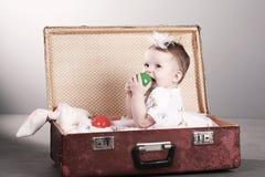 A menina senta-se em uma mala de viagem. fotografia de stock
