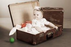 A menina senta-se em uma mala de viagem Foto de Stock Royalty Free