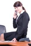 A menina senta-se em uma tabela e fala-se pelo telefone Imagens de Stock