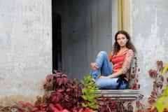 A menina senta-se na abertura do indicador Imagem de Stock Royalty Free