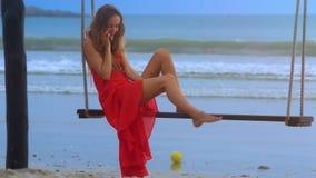 A menina senta-se na areia molhada dos toques do balanço com pé desencapado video estoque