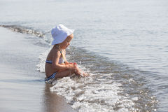 A menina senta-se na borda da água Imagem de Stock Royalty Free