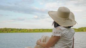 A menina senta-se na borda de um cais de madeira velho filme