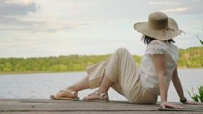 A menina senta-se na borda de uma doca de madeira velha do beliche do cais vídeos de arquivo
