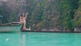 A menina senta-se na borda do barco vídeos de arquivo