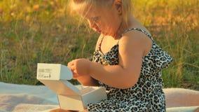 A menina senta-se na cobertura no parque e toma-se moedas da caixa vídeos de arquivo