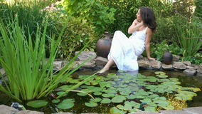 A menina senta-se na costa de uma lagoa vídeos de arquivo
