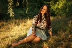 A menina senta-se na grama e nas poses Imagens de Stock