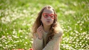 A menina senta-se na grama no grassplot, fundo verde Criança que levanta com vidros e a coroa de sorriso do cartão no prado Menin video estoque