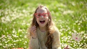 A menina senta-se na grama no grassplot, fundo verde Menina da criança para gastar fora o lazer O melhor conceito do feriado Leva video estoque