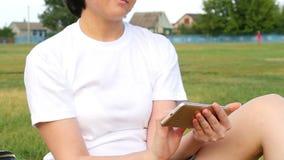 A menina senta-se na grama verde e usa-se o smartphone Uma jovem mulher usa redes sociais Close-up vídeos de arquivo