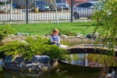 A menina senta-se na ponte através de uma lagoa no parque Fotos de Stock Royalty Free