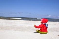 A menina senta-se na praia Fotos de Stock Royalty Free