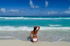 A menina senta-se na praia do mar em um biquini branco Foto de Stock Royalty Free