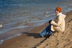 A menina senta-se na praia, um dia ensolarado do outono Fotos de Stock Royalty Free