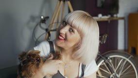 A menina senta-se na sala de visitas e guarda-se um cão pequeno Retrato de uma mulher loura que abraça seus cão e vista de sorris video estoque