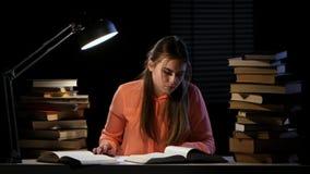 A menina senta-se na tabela e em ler um livro Fundo preto filme