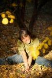 A menina senta-se na terra no parque do outono Foto de Stock Royalty Free