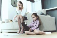A menina senta-se no assoalho com Teddy Bear Near Upset Mom imagens de stock royalty free
