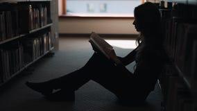 A menina senta-se no assoalho e lê-se um livro na biblioteca filme