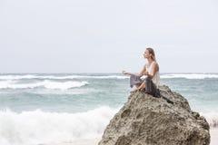 A menina senta-se no beira-mar na rocha e em meditar na pose da mulher da ioga Fotos de Stock Royalty Free