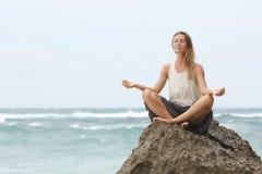 A menina senta-se no beira-mar na rocha e em meditar na pose da mulher da ioga Imagens de Stock Royalty Free