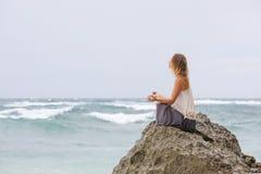 A menina senta-se no beira-mar na rocha e em meditar na pose da mulher da ioga Foto de Stock Royalty Free