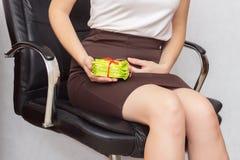 A menina senta-se no escritório em uma cadeira do computador e aferra-se ao abdômen mais baixo, em sua outra mão uma pilha com al foto de stock royalty free