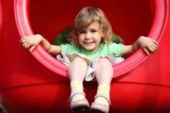 A menina senta-se no furo plástico no campo de jogos foto de stock