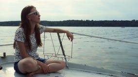 A menina senta-se no iate do barco de vela aprecia o mar em um navio grande ao navegar no mar video estoque