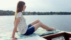 A menina senta-se no iate do barco de vela aprecia o mar em um navio grande ao navegar no mar vídeos de arquivo