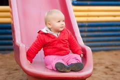 A menina senta-se no lado após desliza para baixo Foto de Stock