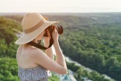 A menina senta-se no monte e toma-se imagens na perspectiva da imagens de stock