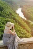 A menina senta-se no monte e toma-se imagens na perspectiva de uma floresta e de um rio meandrar Imagens de Stock Royalty Free