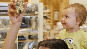 A menina senta-se no pai Shoulders e olha-se Toy Crocodile vídeos de arquivo