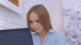 A menina senta-se no portátil contra a árvore do White Christmas vídeos de arquivo