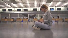 A menina senta-se no terminal no assoalho dos trabalhos do aeroporto com um port?til ao esperar o voo vídeos de arquivo