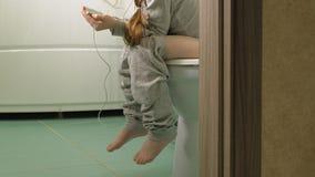 A menina senta-se no toalete e usa-se o telefone video estoque